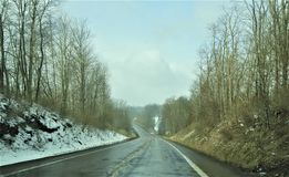 Iced over road going down a hill in Western Pennsylvania stock image