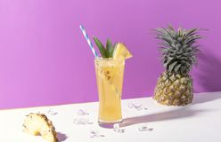 Iced pineapple punch cocktail in glass on color background. summer drink.  royalty free stock photo