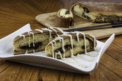 Iced raisin nut bread. Nicely plated iced raisin nut bread with loaf and knife in backgound on wood cutting board Stock Images