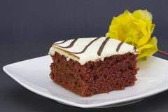 Iced red velvet cake on white platter accented with yellow prick Royalty Free Stock Photo
