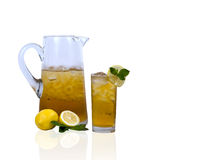 Iced Tea. An ice cold pitcher and glass of iced tea garnished with fresh mint and sliced lemons on white background with reflection stock photo