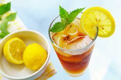 Iced tea. Tall glass of iced tea with lemon and fresh mint Stock Image
