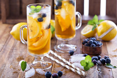 Iced tea with blueberries and lemon slices. Iced tea with blueberries, lemon slices and mint on rustic background Stock Images