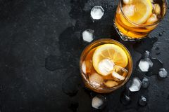 Iced tea. Cold iced tea with lemon and ice cubes over black stone background, copy space, top view. Iced summer drink royalty free stock photos