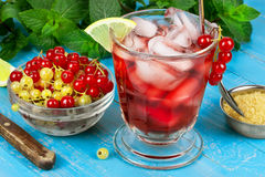 Iced tea. With currants, mint and lemon over blue wooden background Stock Photography