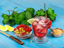 Iced tea. With currants, mint and lemon over blue wooden background Stock Photo
