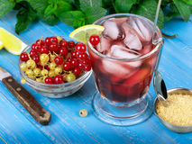 Iced tea. With currants, mint and lemon over blue wooden background Royalty Free Stock Image