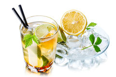 Iced tea. In the glass decorated with leaves near a transparent saucer with tea ingredients Stock Image