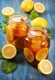 Iced tea with lemon. In glass jars royalty free stock images