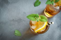 Iced tea. With lemon, mint and ice cubes over gray concrete background, copy space. Iced cold summer drink stock photos