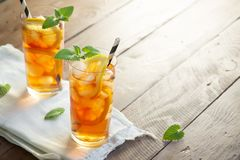 Iced tea. With lemon, mint and ice cubes over wooden background, copy space. Iced cold summer drink royalty free stock photos