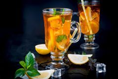 Iced tea with lemon and mint. Iced tea with slices of lemon, mint and ice on a black background, copy space royalty free stock images