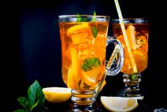 Iced tea with lemon and mint. Iced tea with slices of lemon, mint and ice on a black background, copy space royalty free stock photography