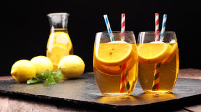 Iced tea with lemon slices, mint and ice. On rustic background Royalty Free Stock Images
