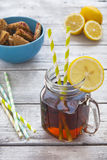 Iced tea with lemon slices and raspberry chip cookies on rustic Stock Photography