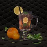 Iced tea with mint, lemon and ice. Iced tea with mint and lemon. Glass glass stands on a black padded surface, lay next to oranges royalty free stock image