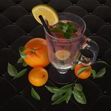 Iced tea with mint, lemon and ice. Iced tea with mint and lemon. Glass glass stands on a black padded surface, lay next to oranges royalty free stock images