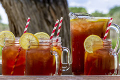 Iced Tea at Picnic in Grand Junction, Colorado. Pitcher and mason jar mugs filled with iced tea and lemons sitting on picnic table with red checked tablecloth royalty free stock images