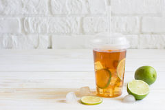 Iced tea in a plastic cup with straw with slice of lime. White w. Ooden plank background stock photos