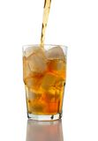Iced Tea Pouring over Ice. Iced tea pouring into a glass of ice on a white background - clipping path included royalty free stock photos