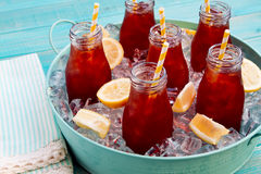 Iced Teas in Ice Filled Tray. Glass milk bottles filled with iced tea and fresh lemon with yellow swirled straw on ice in round blue metal tub sitting on bright Stock Photo