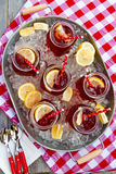 Iced Teas in Ice Filled Tray. Mason jar mugs filled with iced tea and fresh lemon on ice in steel tub sitting on red gingham table cloth on wooden table from Royalty Free Stock Image