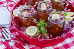 Iced Teas in Mason Jars on Ice. Red tray filled with ice holding mason jar mugs filled with lemon iced tea and red swirled straws sitting on picnic table covered royalty free stock images