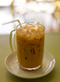 Iced Thai tea in a glass cup. A glass cup of iced Thai tea with ice cubes and a straw on a saucer set in a restaurant royalty free stock photos
