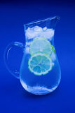 Iced water. Jug of iced water with lemon wheels - focus around the lip of the jug with intentional blue hue stock photography