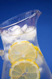 Iced water on blue. Close up of a jug of iced water with lemon wheels - shallow dof stock images