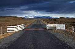 Iceland. Deserted country road leading into the horizon and white fence stock photography