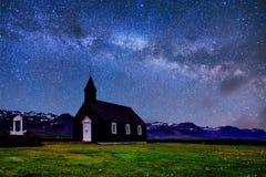 iceland bergsikt Fantastisk stjärnklar himmel och den mjölkaktiga vägen Härlig svart träkyrka i Budir royaltyfri fotografi