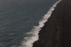 Aerial view of Iceland ocean wave cresting on black sand beach stock photo