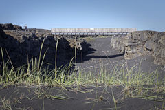 Iceland: Bridge between two continents. Bridge built between two continents where two plates getting further from each others is causing a widening crack in the stock photography