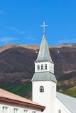Iceland Church. On bright blue sky and mountains background Royalty Free Stock Images