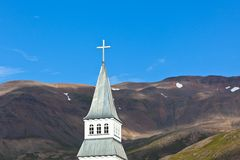 Iceland Church Steeple. On bright blue sky and mountains background Stock Images