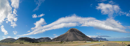 Iceland clouds over mountain. Iceland mountain cloudscape beautiful elongated clouds over Icelandic hills on a sunny blue sky summers day picturing the ring road Royalty Free Stock Photo