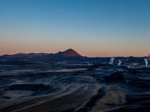 Iceland - Cosmic landscape. A volcanic, geothermal landscape captured during the sunrise. First beams of the sun reach the top parts of volcano. Smoke coming out stock photos