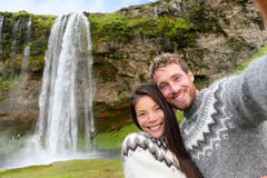 Iceland couple selfie wearing Icelandic sweaters. By Seljalandsfoss waterfall on Ring Road in beautiful nature landscape on Iceland. Woman and men model in Stock Photo