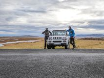 Iceland - A couple with skeleton face shields standing in front of a car. A couple standing on the side of a smaller car. They are wearing a skeleton face royalty free stock images