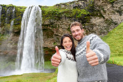 Iceland couple thumbs up wearing Icelandic sweater. By Seljalandsfoss waterfall on Ring Road in beautiful nature landscape on Iceland. Woman and men model in Royalty Free Stock Photography