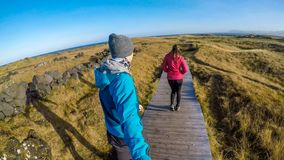 Iceland - A couple walking on a path across the grassland royalty free stock photo