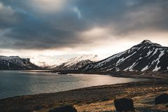 Iceland dramatic sky with snow capped mountain at ocean lake water. Southern side if the country. royalty free stock photography