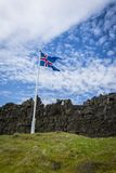 Iceland flag, grass and volcanic rocks at Thingvelir. Icelanc flag. Grass and volcanic rocks at Thingvelir Royalty Free Stock Photos