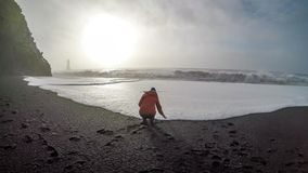 Iceland - A girl playing with waves at black sand beach stock photos