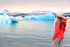 Iceland glacial lagoon - woman looking at view. Iceland glacial lagoon. Woman looking at view of Icelandic glacier lake Jokulsarlon. Beautiful young multiracial stock photo