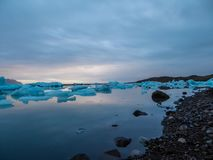 Iceland - Glacier lagoon with drifting icebergs. Beautiful glacier lagoon, with pebbly shore. Thousands of icebergs drifting lazily towards the sea, shining in royalty free stock photo