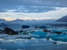 Iceland - Glacier lagoon with drifting icebergs and the glacier itself in the back. Beautiful glacier lagoon. Thousands of icebergs drifting lazily towards the stock photo