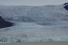 Iceland glacier light blue and black. Serac cloudy day in front of lagoon Stock Photography