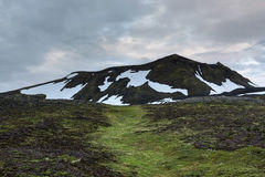 Iceland green hills with snow patches in. Stock Photography